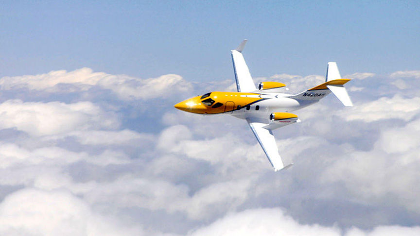 yellow and white Honda jet flying above clouds